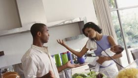 Couple in the kitchen together, busy mom on telephone