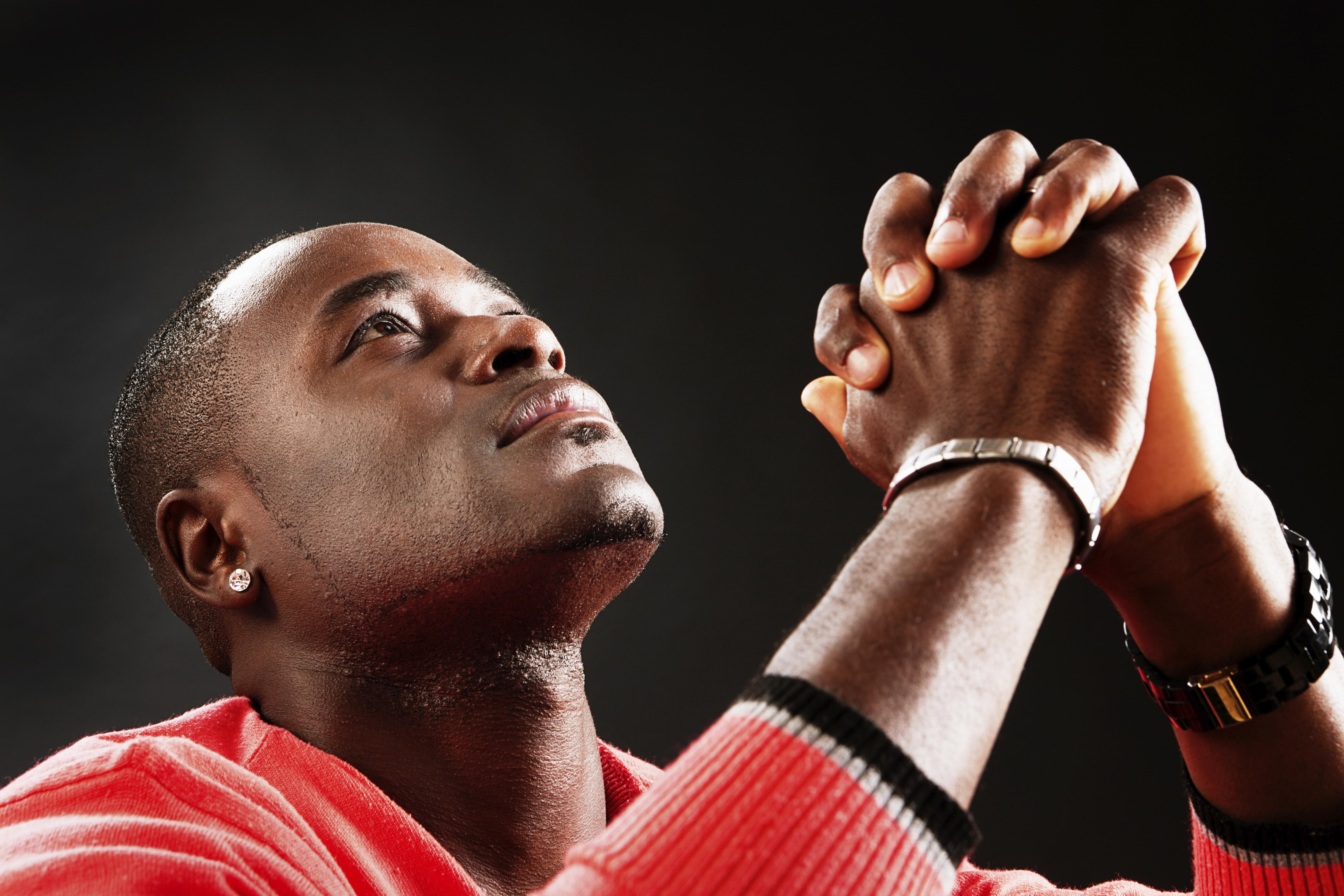 'Young man looks up, hands clasped, praying fervently'