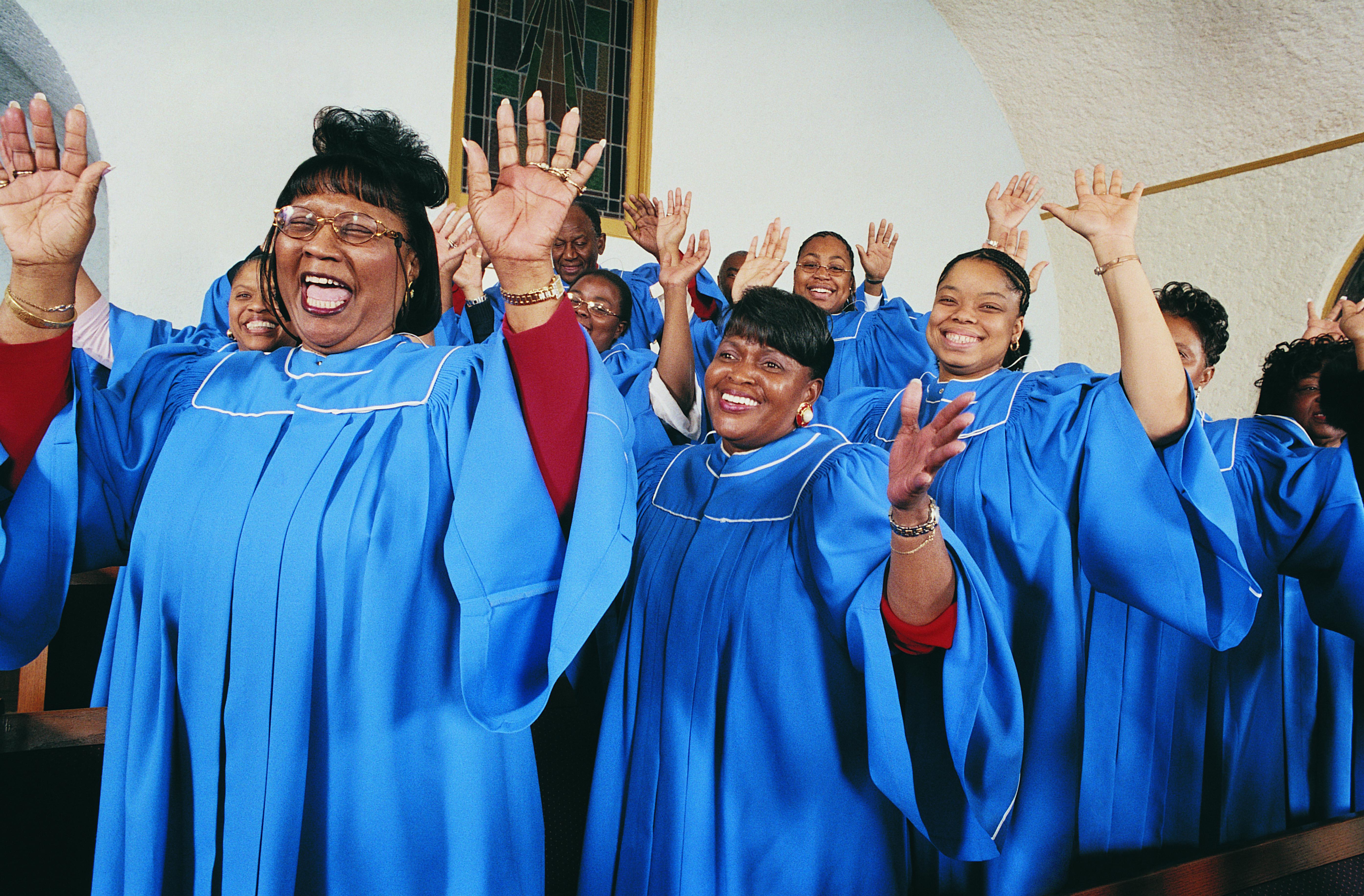 Twelve Gospel Singers With Raised Hands Singing in a Church Service