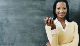 Portrait of a Teacher Standing in Front of a Blackboard Eating an Apple