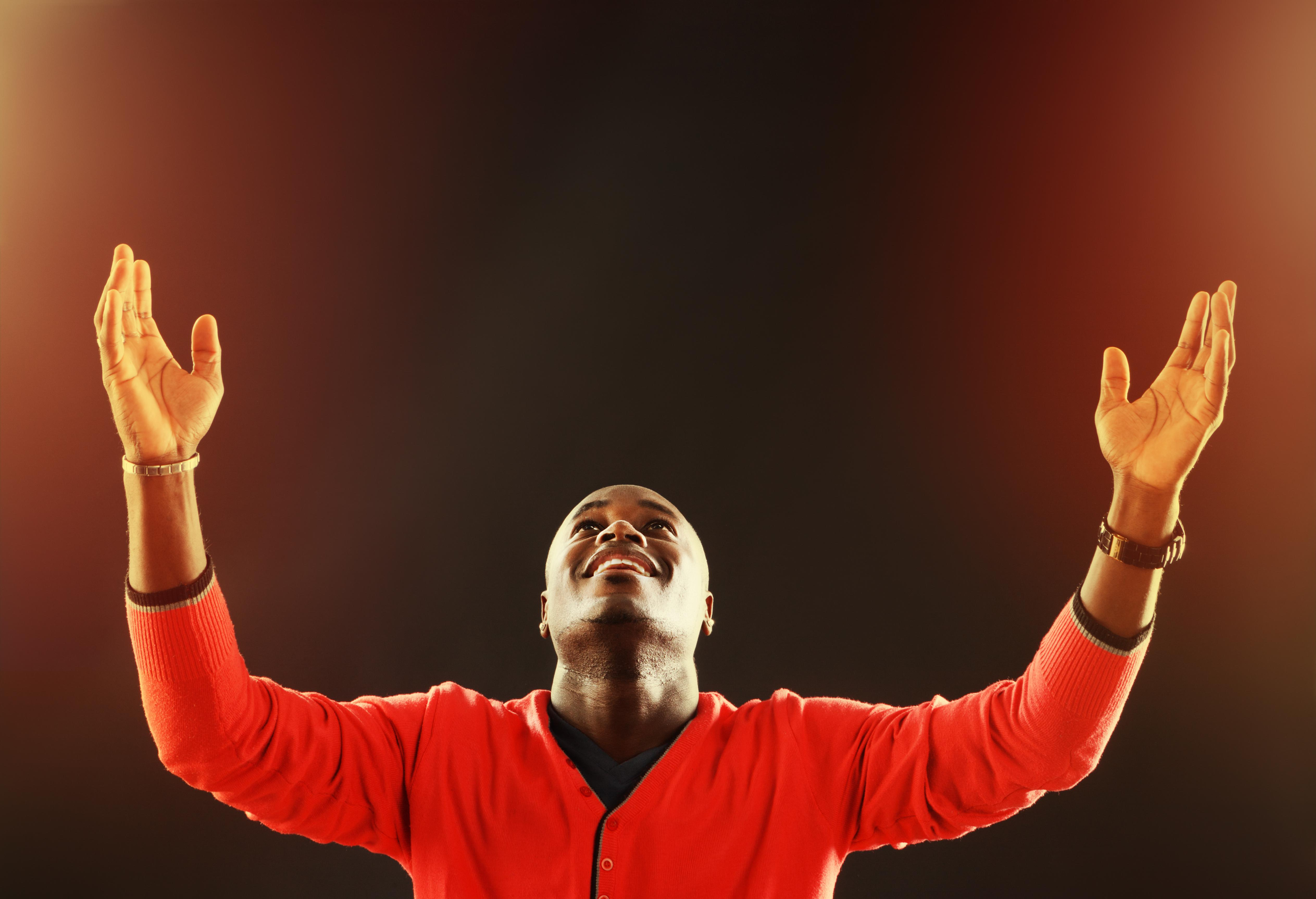 Inspired young man looks up, his hands raised in prayer