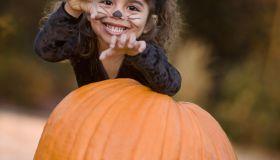 Girl (4-5) in cat costume standing behind pumpkin, portrait