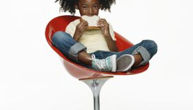 Girl (6-7) sitting on chair, eating peanut butter sandwich, portrait