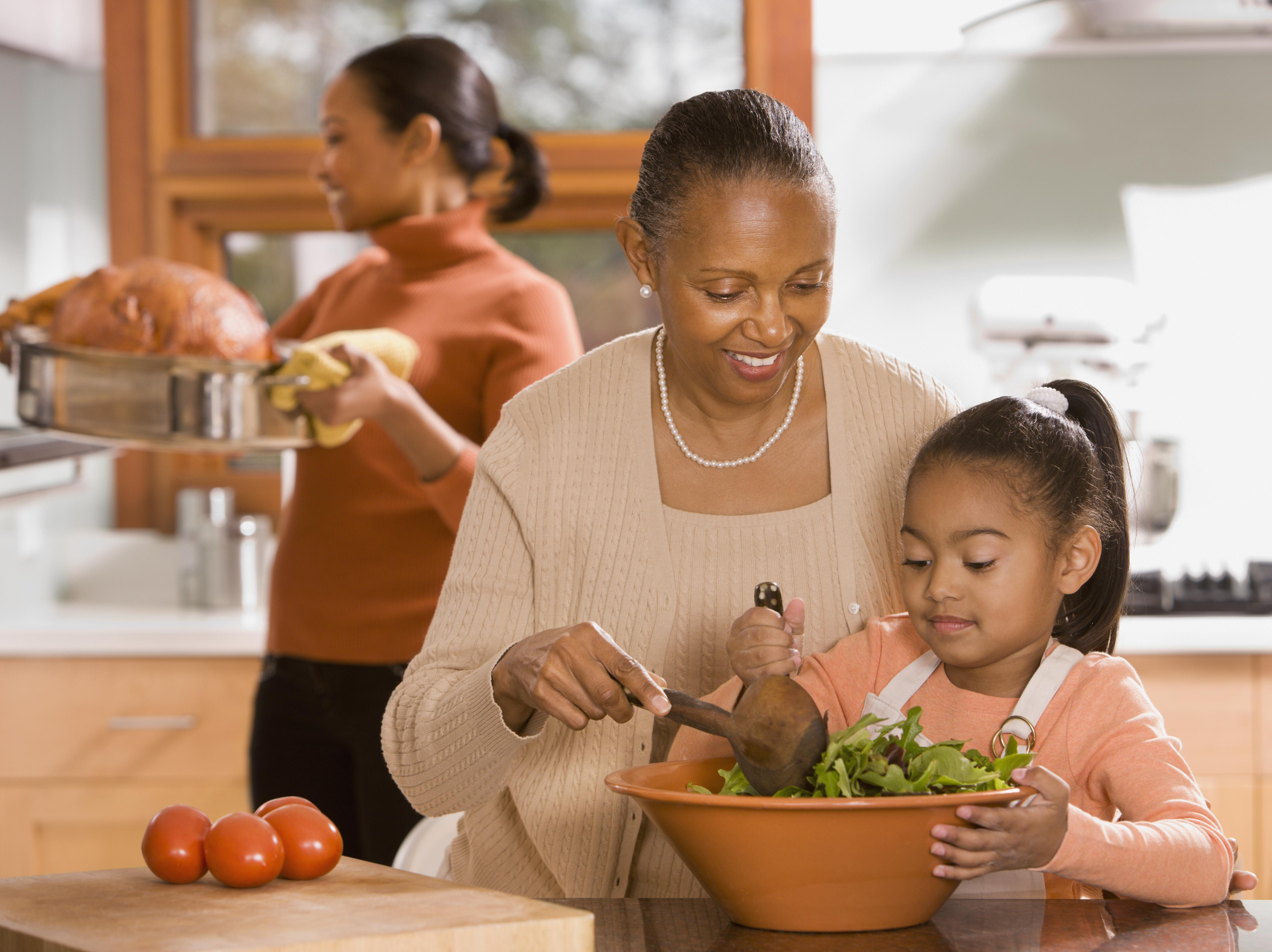 African grandmother, mother and daughter preparing food