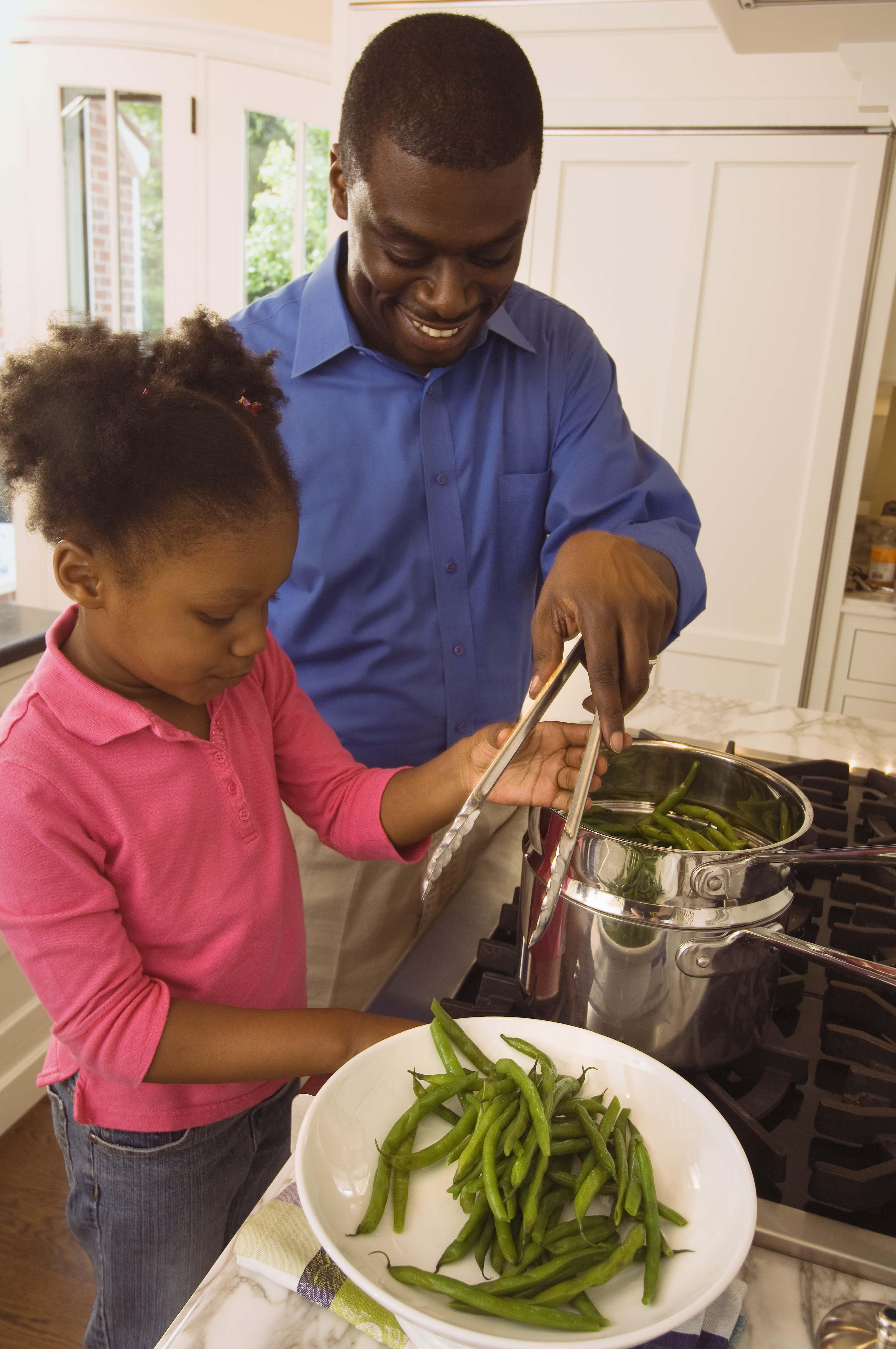 Father and daughter cooking greens