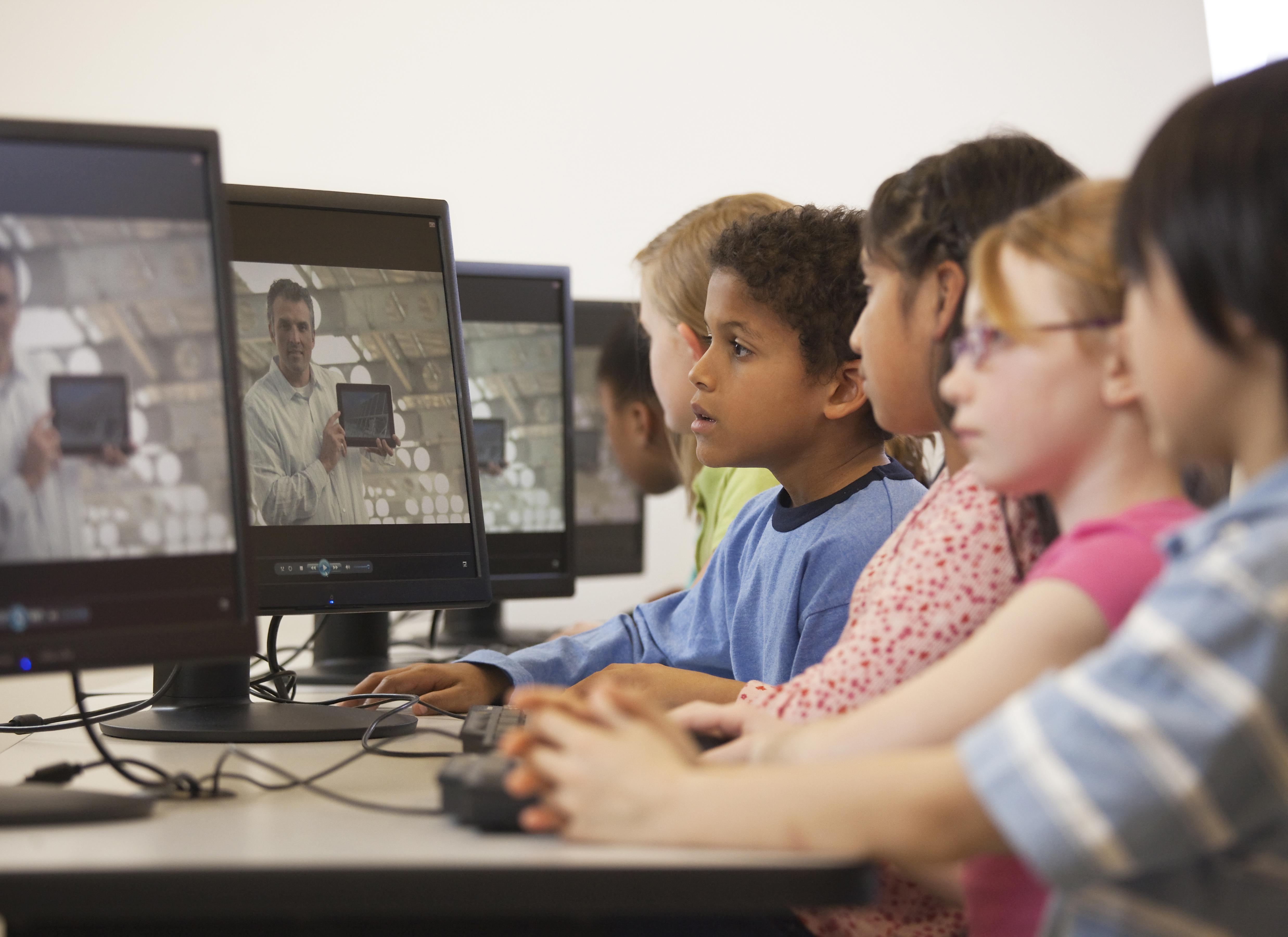 Children watching online instruction in computer lab