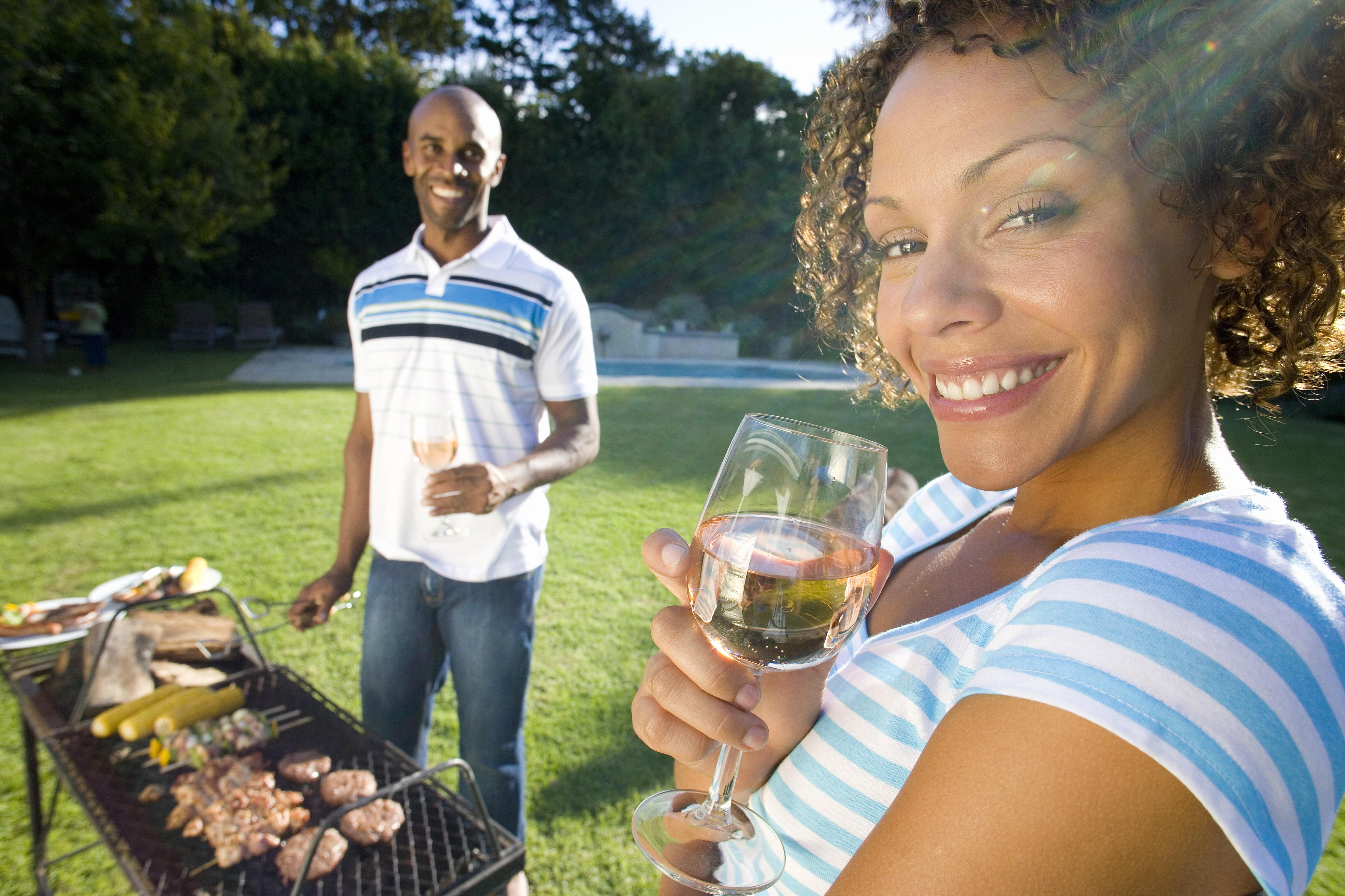 Couple having barbeque outdoors, woman holding glass of wine smiling in foreground