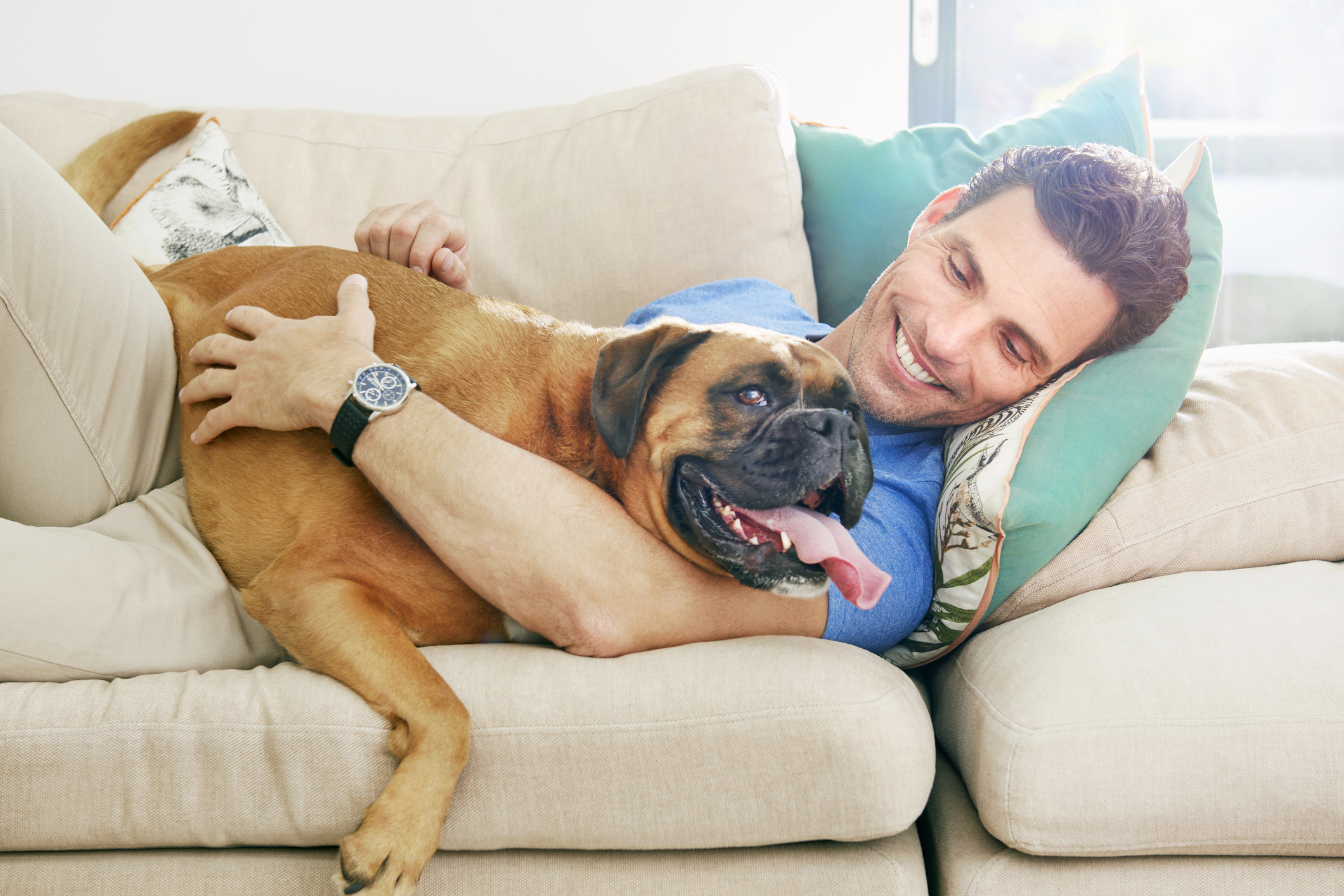 Man lying down cuddling bid dog on the sofa