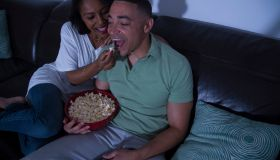 Couple watching television with popcorn on sofa