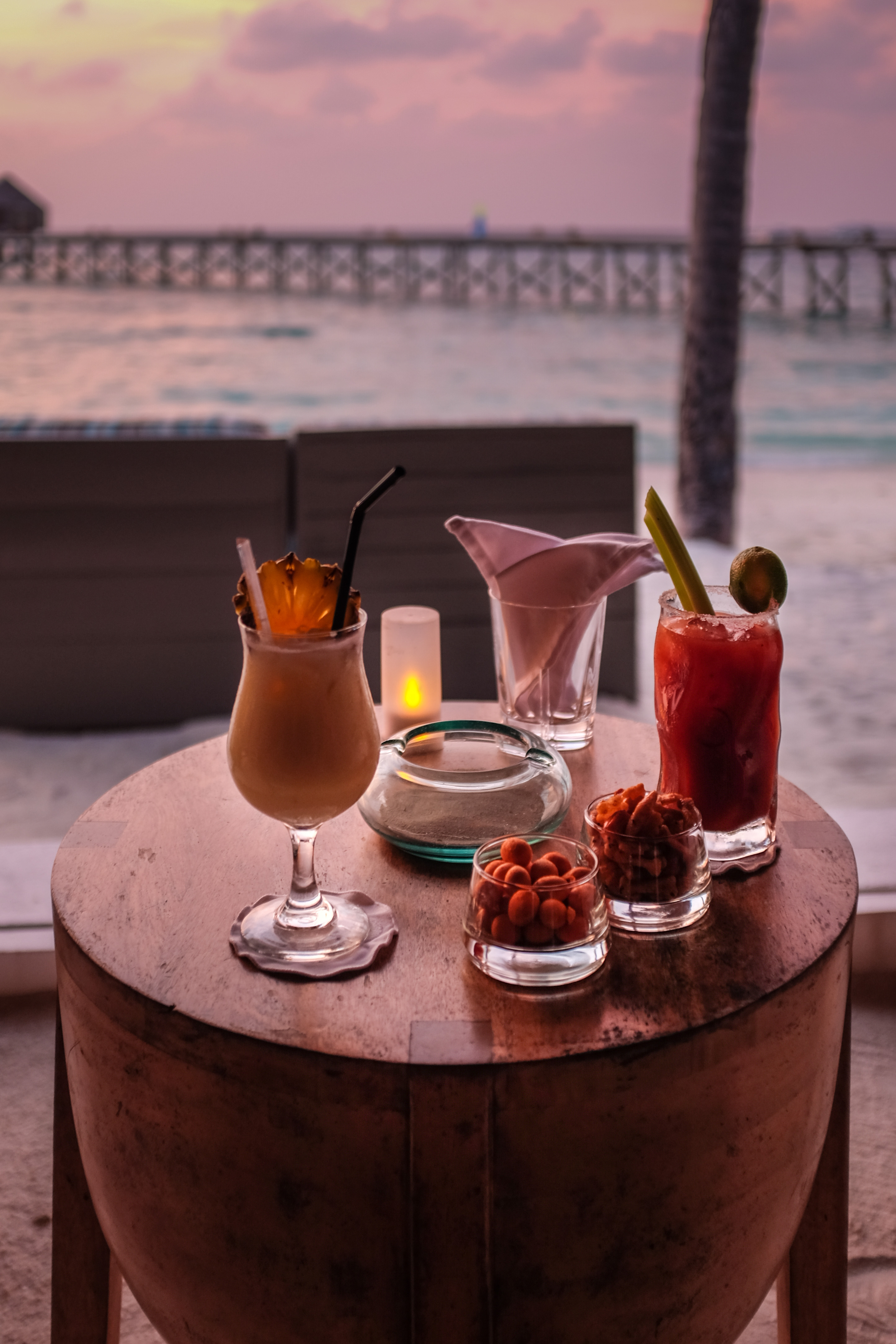 Tropical cocktails are served at the beach-front bar of a...