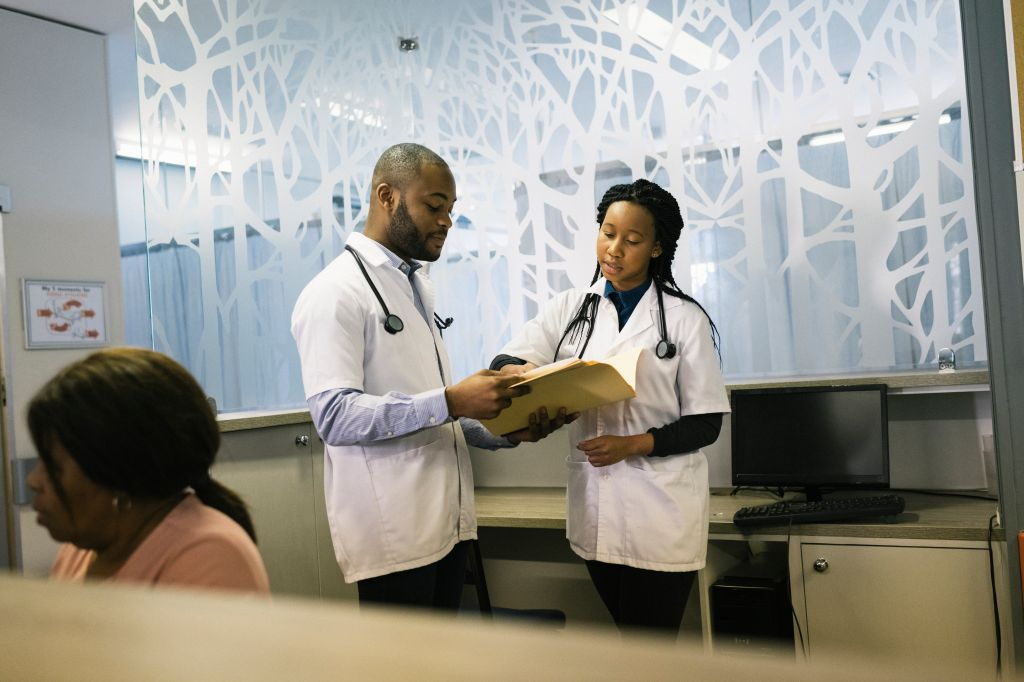 Young African doctors discussing files in clinic reception