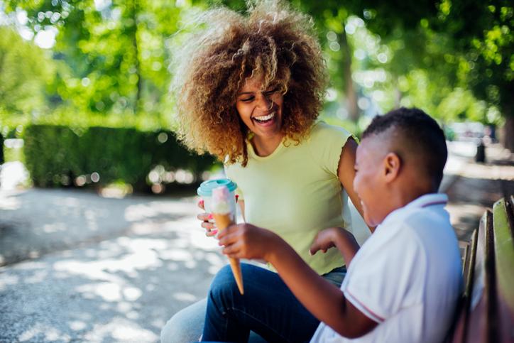 Happy woman having ice cream with son