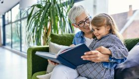 Grandmother sitting on couch with granddaughter, reading book together