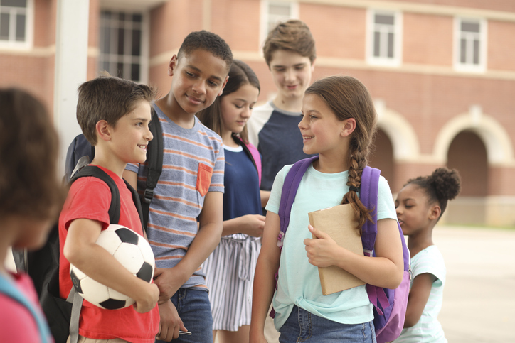 Group of school children, friends talking together on campus.
