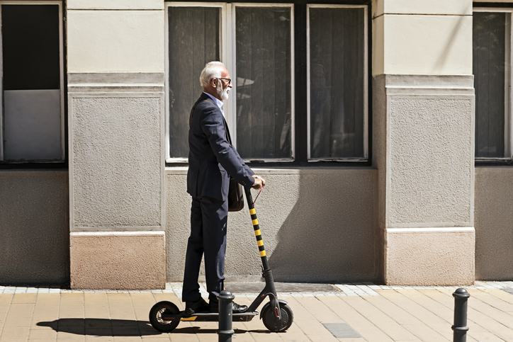Senior Businessman riding a scooter in the city