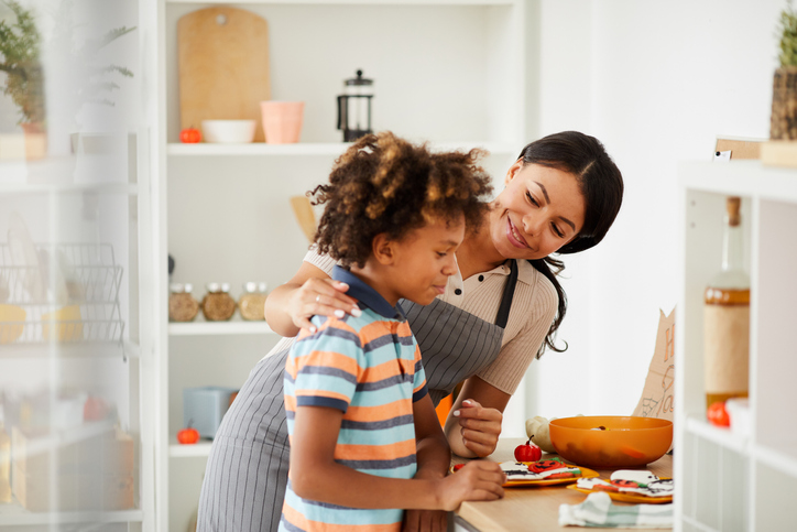 Positive young black mother touching shoulder of son while talking to him in kitchen, they preparing treats for Halloween party
