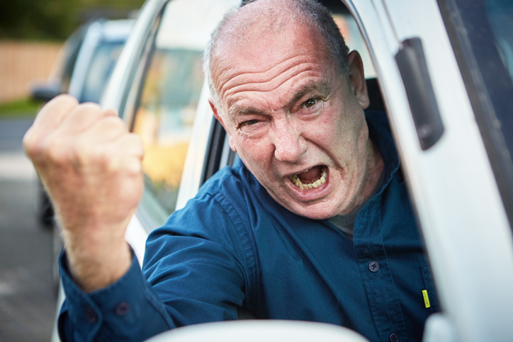 Road rage: furious senior male driver shaking fist and shouting
