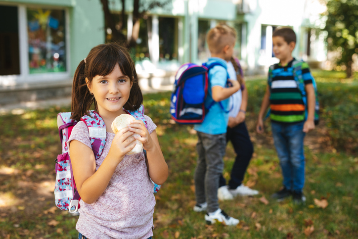 Little girl eating sandwich in a school yard