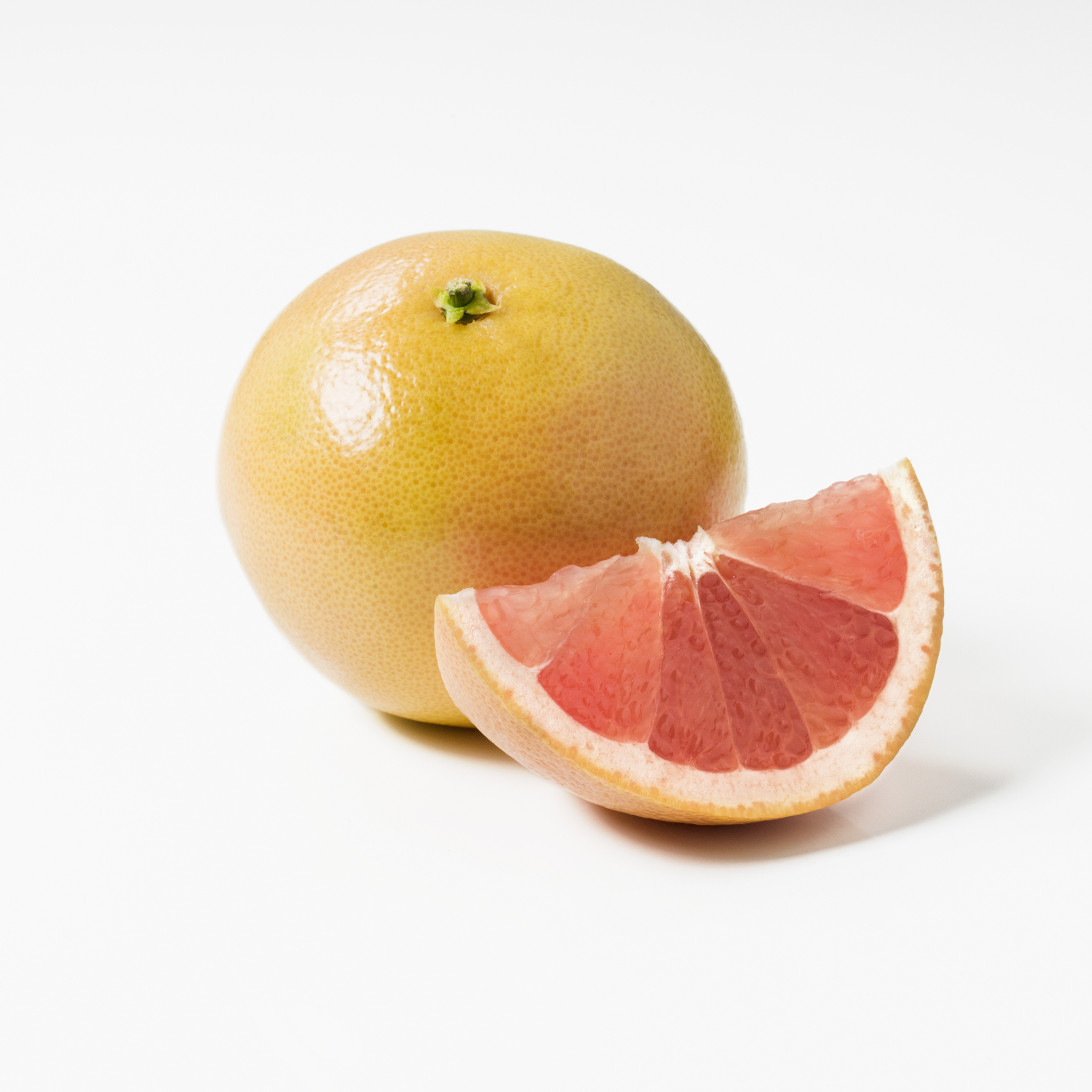 Whole grapefruit and a slice on a white background
