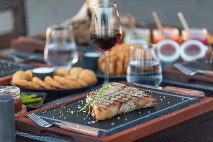 Steak House outdoor table with variety meat dishes - Hotel Luxury Restaurant