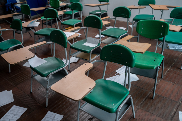 Empty classroom with papers on the floor at a school