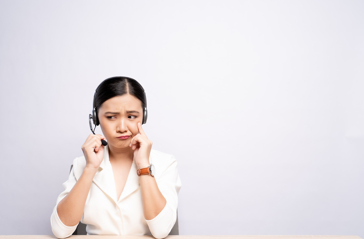 Female Customer Service Representative Talking On Headset While Sitting At Desk Against White Background