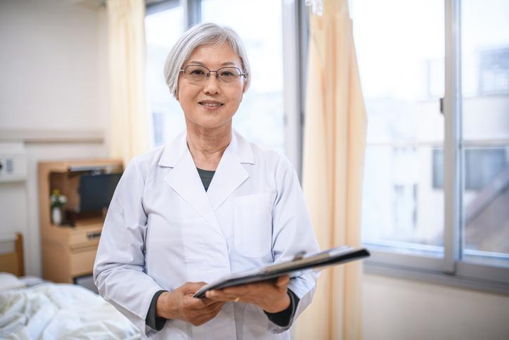 Relaxed Senior Female Japanese Doctor in Hospital Room