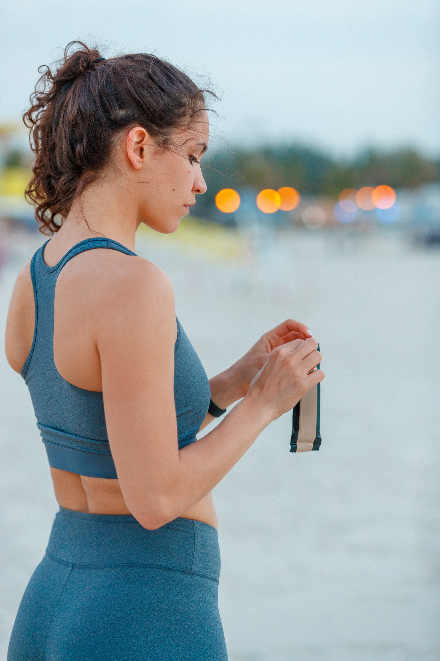 Female jogger opening a protein bar