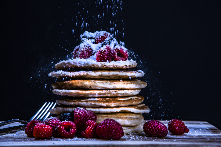 Stack of pancakes with powdered sugar and raspberries