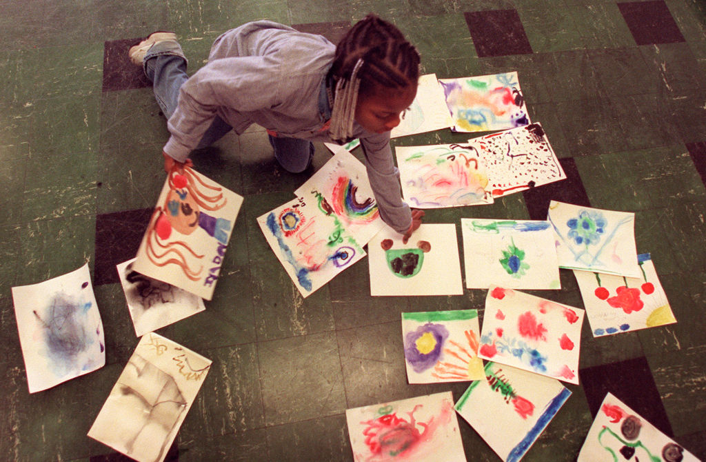 GENERAL INFORMATION: Central Lutheran Church runs an after-school reading program for homeless kids which includes other activities, as well. IN THIS PHOTO: Minneapolis, Mn., Weds., Mar. 21, 2001--Eight-year-old Iyeisha Griffen picks up her paintings out
