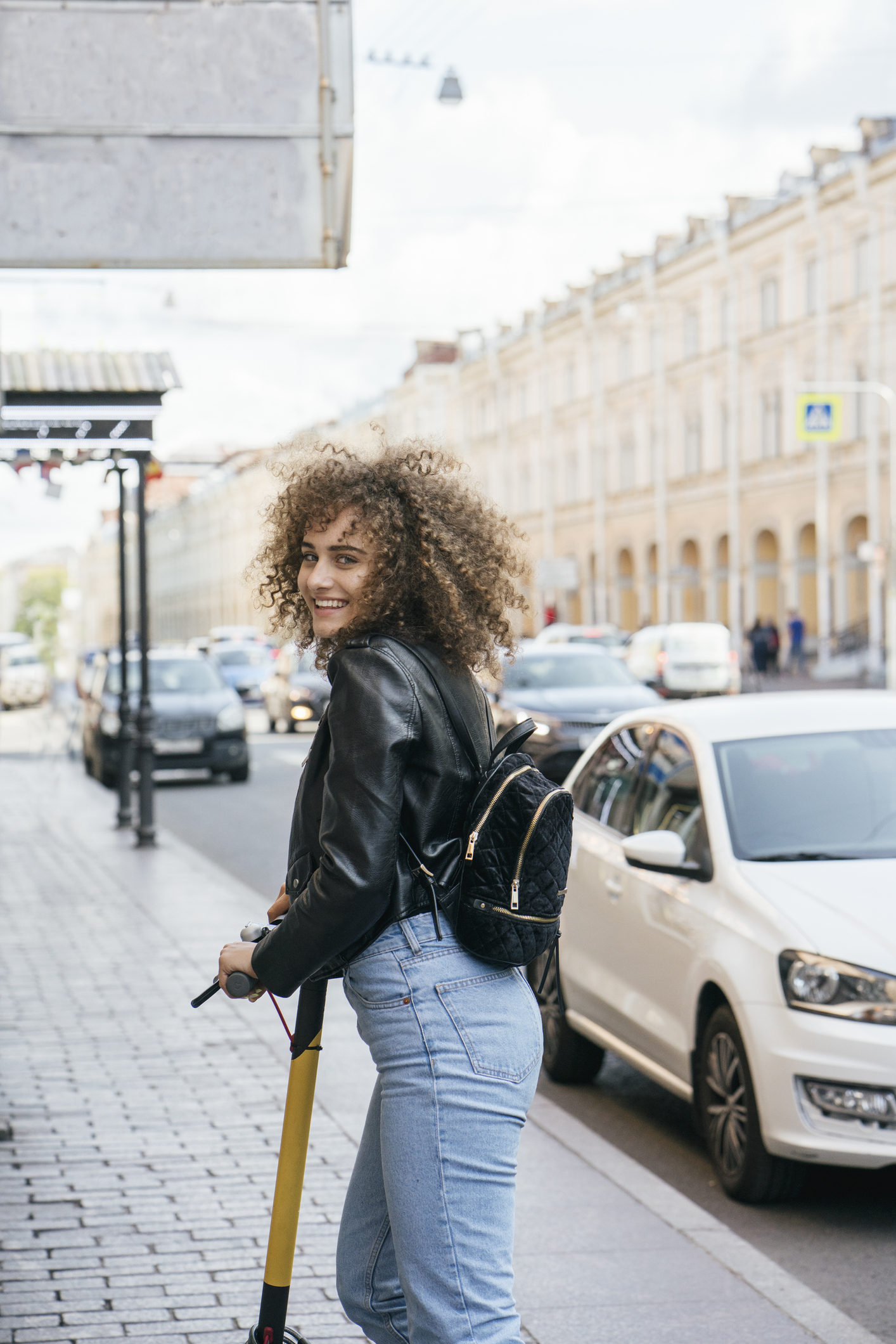 Portrait of smiling teenage girl with scooter standing on pavement