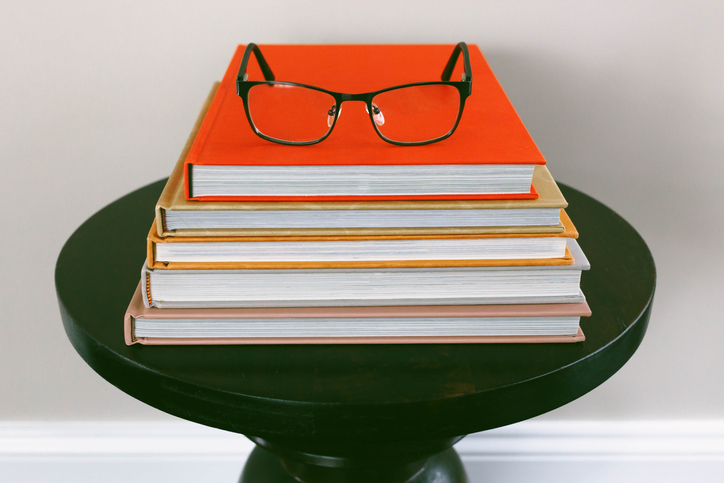 Stack of Books on Side Table with Reading Glasses on Top
