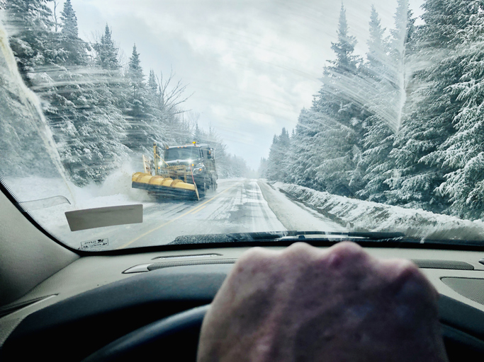 Man driving car during winter in Rangeley, Maine with snowplow coming down road