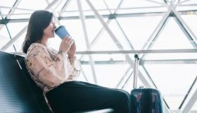 A tourist enjoy her coffee while waiting her flight in departure zone