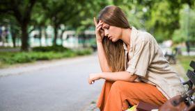 Young sad female student having a headache.