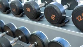 Rows of black metal dumbbells in the gym, selective focus.
