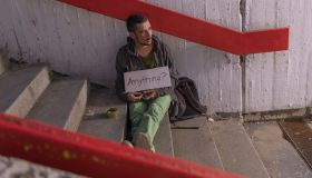 Poor Beggar Sitting on the Stairs and Asking any Kind of Help