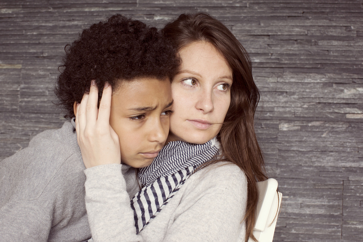 Mother consoling upset young son, portrait