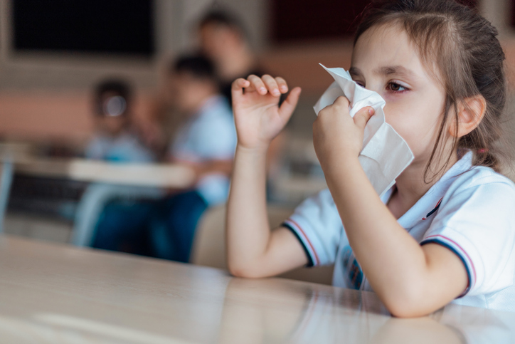 Preschooler wiping nose with tissue