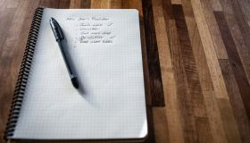 New year's resolution written on a notebook, and a pen on a wooden table