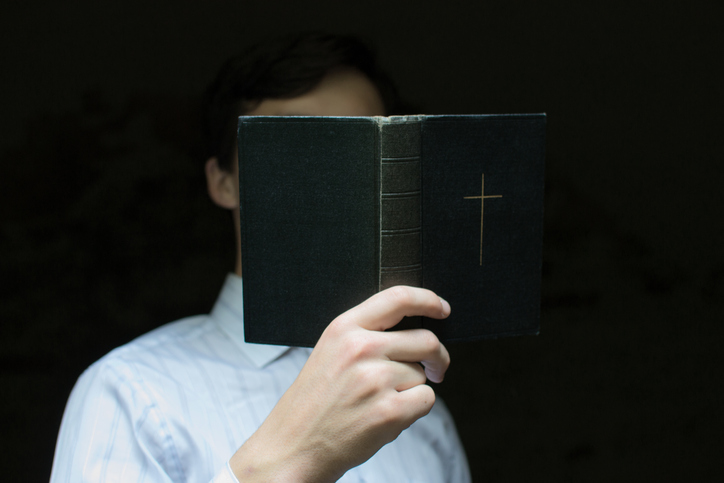 Close-Up Of Man Reading Bible Against Black Background