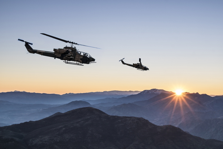 AH-1 Cobra Attack helicopters flying over mountains at sunrise