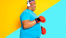 Overweight black man practices exercise and boxing and listens to music on his headphones