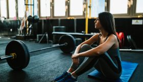 Woman resting after lifting weights in the gym