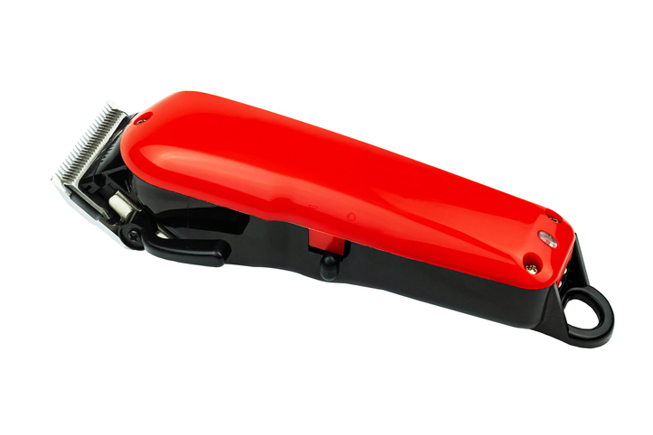 Close-Up Of Red Hair Clipper Over White Background