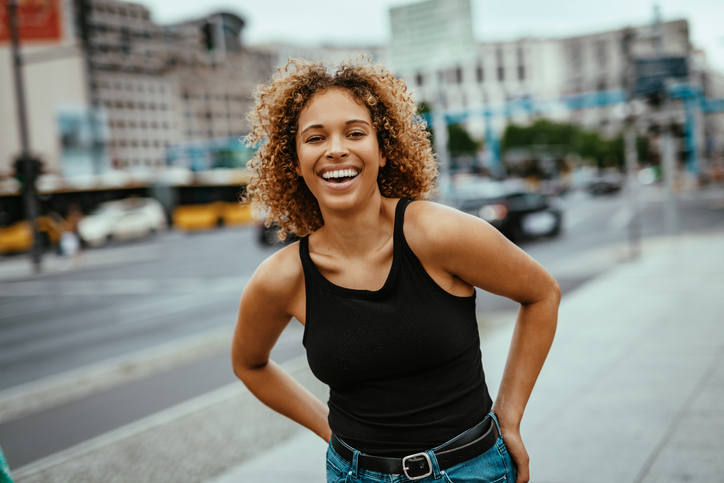 Portrait of mixed race curly woman in city