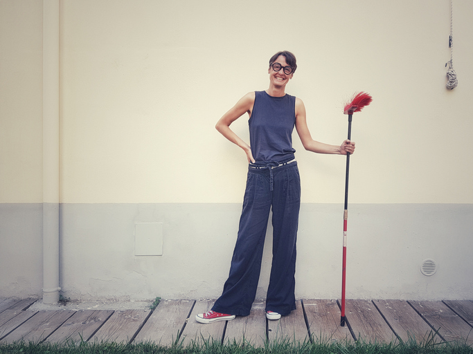 Portrait Of Smiling Woman Holding Broom While Standing Against Wall