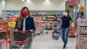Shoppers seen wearing protective face masks as they shop in...