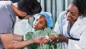 Doctor, nurse helping girl sitting on hospital bed