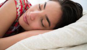 Sleeping woman lying down on bed